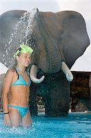 Girl being sprayed with water from model elephant Stock Photo - Premium Royalty-Freenull, Code: 6114-06661739