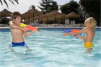 Boys fighting with water pistols Stock Photo - Premium Royalty-Freenull, Code: 6114-06661746