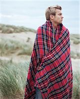 Young man on beach wearing blanket Stock Photo - Premium Royalty-Freenull, Code: 6114-06663609