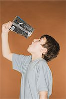 preteen open mouth - Boy emptying crisp packet into his mouth Stock Photo - Premium Royalty-Freenull, Code: 6114-06663940