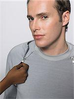 Man having his sweater unzipped Stock Photo - Premium Royalty-Freenull, Code: 6114-06663970