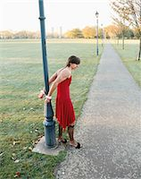Man handcuffed to lamp post wearing red dress Stock Photo - Premium Royalty-Free, Artist: Cultura RM, Code: 6114-06664213