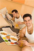 Homosexual couple eating breakfast in bed Stock Photo - Premium Royalty-Freenull, Code: 6114-06664260