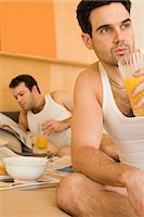 Homosexual couple eating breakfast in bed Stock Photo - Premium Royalty-Freenull, Code: 6114-06664300