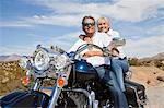 Senior couple on desert road sitting on motorcycle looking at camera Stock Photo - Premium Royalty-Free, Artist: Allan Baxter, Code: 693-06667816