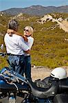 Senior couple embrace next to motorcycle in the desert Stock Photo - Premium Royalty-Free, Artist: Blend Images, Code: 693-06667823