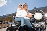 Senior couple riding a motorcycle together in a rural landscape Stock Photo - Premium Royalty-Free, Artist: Westend61, Code: 693-06667825