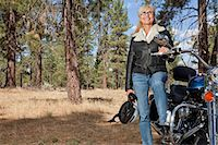 Senior woman poses with motorcycle in forest Stock Photo - Premium Royalty-Freenull, Code: 693-06667830