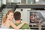 Portrait of young Caucasian woman with man watching movie on television in living room Stock Photo - Premium Royalty-Free, Artist: Blend Images, Code: 693-06667999