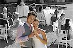 Portrait of newly wedded couple with champagne glasses at wedding reception Stock Photo - Premium Royalty-Free, Artist: Blend Images, Code: 693-06668031