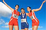Victorious track athletes with arm around each other against sky Stock Photo - Premium Royalty-Free, Artist: Blend Images, Code: 693-06668035