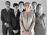 Ambitious businesswoman with team of professionals against gray background Stock Photo - Premium Royalty-Free, Artist: Westend61, Code: 693-06668059
