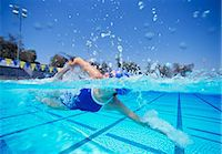 swimming pool water - Female swimmer in United States swimsuit swimming in pool Stock Photo - Premium Royalty-Freenull, Code: 693-06668098