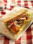 Chicken, onion, pepper, gherkins, cheese slices, lettuce and ketchup in a baguette on a wooden board Stock Photo - Premium Royalty-Free, Artist: CulturaRM, Code: 659-06671352