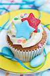 A vanilla cupcake with colourful stars, sugar confetti and blue sugared almonds Stock Photo - Premium Royalty-Free, Artist: John Cullen, Code: 659-06671386