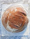 A loaf of bread on paper, on a marble slab, dusted with flour Stock Photo - Premium Royalty-Freenull, Code: 659-06671585