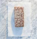 A wholemeal sandwich loaf on paper, on a marble slab, dusted with flour Stock Photo - Premium Royalty-Free, Artist: AWL Images, Code: 659-06671594