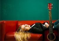Woman Lying on Sofa with Acoustic Guitar Stock Photo - Premium Royalty-Freenull, Code: 600-06675139