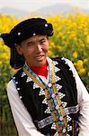 China, Yunnan, Luoping. A man dressed in traditional clothing enjoying the mustard fields at Luoping. Stock Photo - Premium Rights-Managed, Artist: AWL Images, Code: 862-06676198