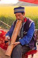 China, Yunnan, Luoping. A man of the Buyi ethnic minority group enjoying a smoke with a large water pipe amongst the mustard fields of Luoping. Stock Photo - Premium Rights-Managednull, Code: 862-06676223