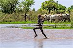 A young Dassanech herdsboy runs across shallow water beside the Omo River. The river bursts its banks annually during heavy rain in the Ethiopian Highlands, Ethiopia Stock Photo - Premium Rights-Managed, Artist: AWL Images, Code: 862-06676696