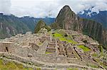 South America, Peru, Cusco, Machu Picchu. A general view of terraces and buildings at the World Heritage listed Inka Historic Sanctuary of Machu Picchu with Huayna Picchu, Wayna Picchu, mountain behind. The site is situated in the Andes above the Urubamba valley Stock Photo - Premium Rights-Managed, Artist: AWL Images, Code: 862-06677257