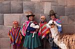 South America, Peru, Cusco. Quechua people standing in front of an Inca wall, holding a lamb and a llama and wearing traditional clothing including a bowler hat, liclla, chullo and poncho    while talking on a cell phone in the UNESCO World Heritage listed former Inca capital of Cusc Stock Photo - Premium Rights-Managed, Artist: AWL Images, Code: 862-06677338
