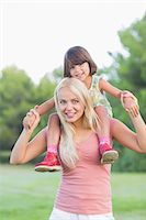 Mother giving daughter a piggy back Stock Photo - Premium Royalty-Freenull, Code: 6109-06684766