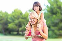 Beautiful mother giving daughter a piggy back Stock Photo - Premium Royalty-Freenull, Code: 6109-06684767