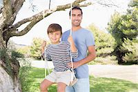 swing (sports) - Portrait of father pushing son on a swing Stock Photo - Premium Royalty-Freenull, Code: 6109-06684813