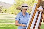 Woman in straw hat painting in the park Stock Photo - Premium Royalty-Free, Artist: Blend Images, Code: 6109-06684849