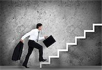 Businessman climbing the stairs to the top Stock Photo - Premium Royalty-Freenull, Code: 6109-06684997