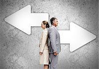 right - Business partners standing back to back on wall with arrows Stoc