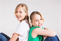 Portrait of Girls Sitting Back to Back in Studio Stock Photo - Premium Royalty-Freenull, Code: 600-06685172