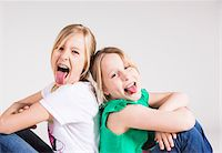 Portrait of Girls Sitting Back to Back and Sticking their Tongues Out Stock Photo - Premium Royalty-Freenull, Code: 600-06685173