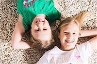Overhead View of Girls lying on Carpet in Studio Stock Photo - Premium Royalty-Freenull, Code: 600-06685175