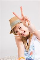 Portrait of Girl wearing Hat and making Peace Sign Gesture in Studio Stock Photo - Premium Royalty-Freenull, Code: 600-06685179