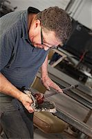 Artist rolling hot glass object with mitts on workbench Stock Photo - Royalty-Freenull, Code: 400-06696177
