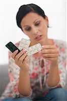 Closeup on pills in hand of concerned young woman Stock Photo - Royalty-Freenull, Code: 400-06699964