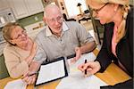 Senior Adult Couple Going Over Papers in Their Home with Agent. Stock Photo - Royalty-Free, Artist: Feverpitched                  , Code: 400-06701047