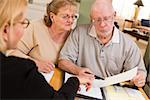 Senior Adult Couple Going Over Papers in Their Home with Agent. Stock Photo - Royalty-Free, Artist: Feverpitched                  , Code: 400-06701049