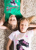 Young Girls Lying Down on a Carpet in Studio Stock Photo - Premium Royalty-Freenull, Code: 600-06701799