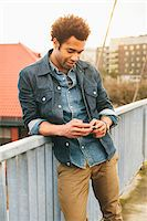 Young man texting on an iPhone in an urban setting. Stock Photo - Premium Rights-Managednull, Code: 700-06701842