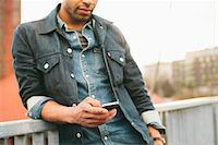 Close-up of young man texting on an iPhone in an urban setting. Stock Photo - Premium Rights-Managednull, Code: 700-06701843