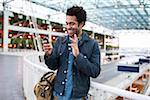 Smiling Man Waving at Cell Phone Camera during Video Chat at the Airport Stock Photo - Premium Rights-Managed, Artist: Boone Rodriguez, Code: 700-06701845
