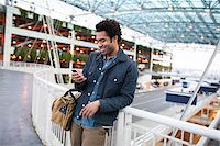 Smiling Man Texting on Cell Phone at the Airport Stock Photo - Premium Rights-Managed, Artist: Boone Rodriguez, Code: 700-06701846