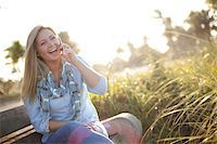 people sitting on bench - Young Woman Sitting on Bench at Beach, using Cell Phone, Jupiter, Palm Beach County, Florida, USA Stock Photo - Premium Royalty-Freenull, Code: 600-06701920