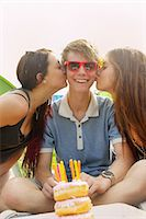 Two Teenage Girls Kissing Teen Boy in front of Birthday Cake Stock Photo - Premium Rights-Managednull, Code: 822-06702179