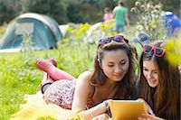 Teenage Girls Lying on Grass Using Tablet Stock Photo - Premium Rights-Managednull, Code: 822-06702180