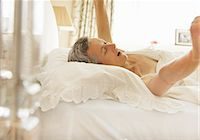Woman in Bed Yawning and Stretching Arms Stock Photo - Premium Rights-Managednull, Code: 822-06702201
